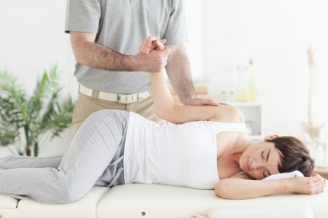 A chiropractor stretches a female customer's arm in his surgery